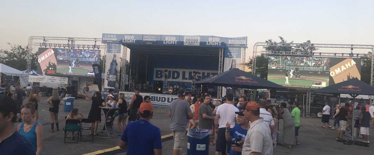 two modular led screen rentals to the left and right of a stage at a baseball tailgate event with large crowd