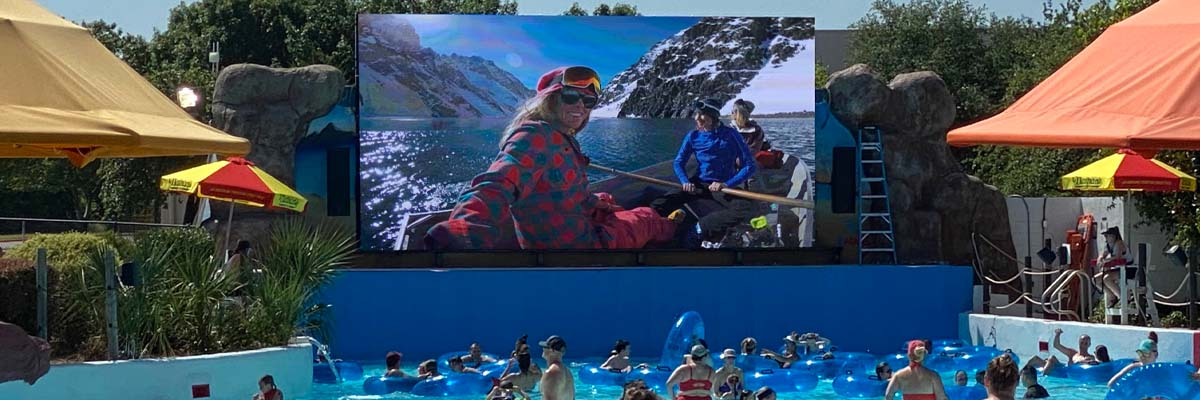 outdoor led screen at hawaiian falls water park displaying three people on a canoe surrounded by mountains. The giant display is located at the end of the wave pool and swimmers are watching it while floating in the water.